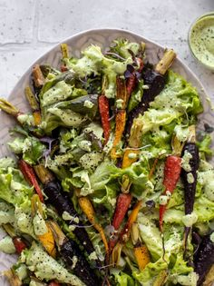 This roasted carrot salad is perfect for spring! Caramely, roasted carrots served over butter greens dressing with green goddess. Simple but delish.