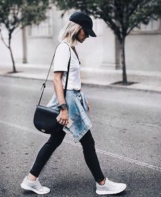 Black vs leggings, white tee, baseball cap. Black bag. Denim jacket tied around waist. Sneakers