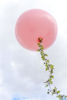 Wedding Inspiration: A floral garland wrapped around balloon strings creates a fairytale feel