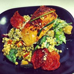 Baked salmon over Caesar salad and a veggie couscous