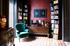Emerald tufted armchair, patterned red wallpaper, and bookshelves in reading nook