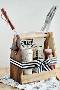 father's day gifts from daughter, tool carrier converted into a barbecue basket, with ketchup, sauces, condiments, beer and grilling tools, on a wooden table with a white background