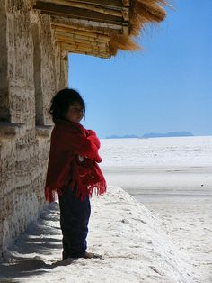 Little girl in Salar de Uyuni, Bolivia. The beautiful Salar de Uyuni is with its 4,085 square miles the world's largest salt flat.