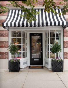 If I were to have a backyard studio I make the front look like this adorable shop.   I love the planters, topiaries, window panes, and black and white stripes