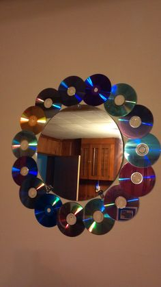 My very own creation hanging in my room. Take an old mirror, and any old CDs. Hot glue CDs together to create a frame. Hang mirror and frame. To hang frame, put nails in the holes to hold in place :)