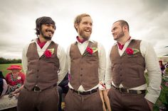 Gorgeous groomsmen in rustic brown suits and striking red buttonholes