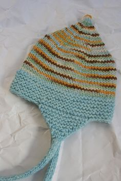 """Ravelry: YummyKnits' Gnomey Hat  Variation: CO 60 sts on worsted weight yarn, size 7 needles   Garter border in contrasting yarn for 1.5""""   Started decreases with K10, k2tog    Earflaps-   Knit 1 extra row before decreasing   continue decreasing every other row till 5 sts remain   i cord for 6"""" (blocked slightly longer)  13"""" (not stretched) at garter border."""