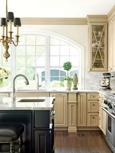 An arched, undressed window allows natural light to pour into the room, giving it a warm, welcoming feel. The arch of the window keeps with the English style and was inspired by the curves of the Westminster Bridge over London's Thames River. The bare window adds a sense of simplicity to the detail-oriented kitchen.