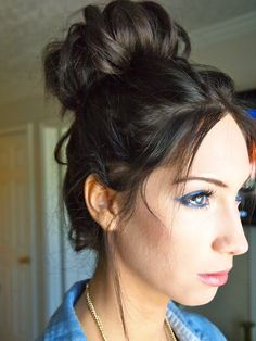 How to accomplish your lovely sock bun:  Step 1:Pull your hair into a high pony.  Step 2:Cut the toe off a sock and roll it into a donut-like shape. Slip it around yourhair.  Step 3:Tuck the ends of your hair under the fabric so it stays put.  Step 4: As if you were rolling your sleeves, roll your hair and the sock together down your ponytail.  Step 5: Tuck in any stray hairs, then spay on some hair spray to help hold the style.