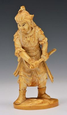 A JAPANESE IVORY OKIMONO carved as standing figure of Bishamonten, dressed in armour and drawing his katana, signed Ikko, late 19th Century,13.5cm high