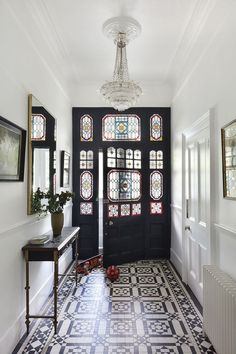 This modern hallway is flooded with light thanks to the stained glass in the door, which perfectly compliments the tiled floor in this stunning urban home. The modern hallway design is complemented with framed pictures and a statement light feature. London Townhouse, Victorian Townhouse, Victorian House Interiors, Townhouse Interior, Victorian Terrace House, Modern Townhouse, London House, Interior Design Victorian House, Victorian House London