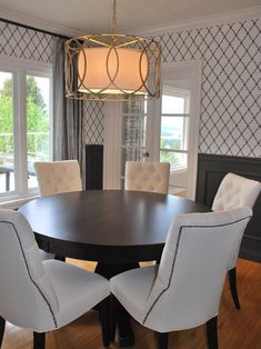 Contemporary dining room with round espresso pedestal dining table and white tufted dining chairs with brass nailhead trim. Troy Lightings 'Sausalito Pendant, black and white quatrefoil wallpaper above charcoal gray wainscoting and silver silk drapes.