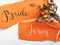 Bright orange torn paper calligraphy place names for a pop of colour
