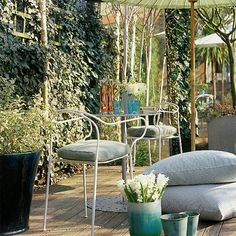 To give a small garden a sense of space, add mirrored panels to reflect natural light and make the area feel larger. A cake table and chairs from Exterior:Interior are shaded by a pastel parasol from The Urban Garden to make an inviting relaxing space. Coloured glassware and planters and over-sized striped floor cushions complete the look.