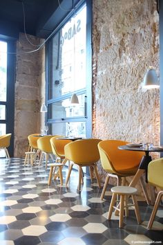 Cafe in Barcelona:  High ceilings, exposed stone providing texture, lots of natural light, but with pops of color and pattern