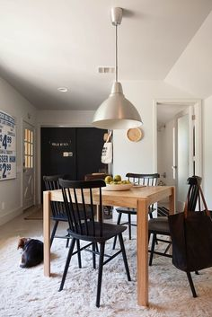 How to create a dining nook in a small, open layout. Wooden square table with black windsor chairs and an industrial Ikea pendant.