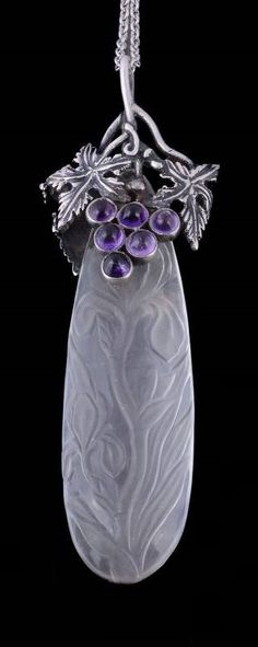 An Arts and crafts carved rock crystal pendant attributed to Amy Sandheim, circa 1930. The pear shaped rock crystal carved with irises, to a silver amethyst and chrysoprase set grape and vine leaf surmount, 8.9cm long.