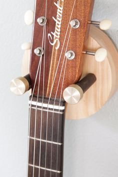 """The new all wood Hyla is a simple, stylish way to wall-mount your guitar. The solid wood disc rotates on a central axis, adjusting to your headstock. Leather details pad the substantial 3/8"""" thick metal prongs with polished brass caps.  Finish Options: Douglas Fir or Natural Walnut"""