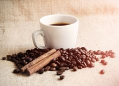 Cup of coffee with roasted beams and cinnamon sun flare - stock photo