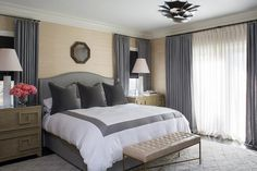 Sophisticated bedroom features walls clad in tan grasscloth lined with a gray camelback bed with ...