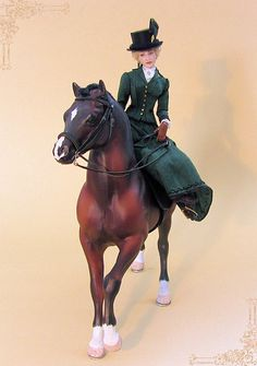 She is dressed in a riding habit made of  green silk. On the skirt a   border in black is hand embroidered.