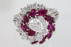 A DIAMOND AND RUBY CLUSTER RING, centre pear shaped diamond: 0.75ct approx. F/G…