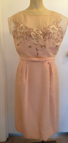 Grabois 1950's silk and linen dress with built in camisole and slip. Beautiful sheer silk top with beading in the front and back. Matching belt with bowtie closure. Lace and cut out floral design has raffia like material sewn in to make the flowers come to light. Light pink, salmon pink would be the best way to describe the color