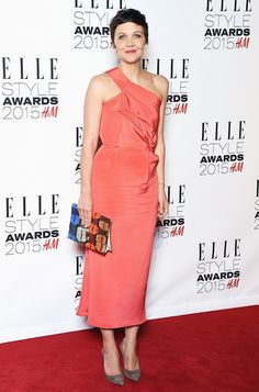 Maggie Gyllenhaal wears a one-shoulder coral dress and carries a bright clutch.