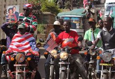 People on motor bike's celebrate American President Barack Obama's visit to Kenya by holding up a photo, left,  of the president and his wife ...