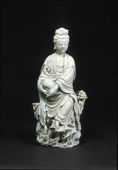 Chinese goddess Guanyin, the Compassionate Bodhisattva (literally 'enlightened being'), sitting on a rock. It was made at Dehua in Fujian province, in southern China