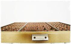 Eine schöne alte Schublade aus der Druckerei. Der Setzkasten hat an jedem Fach eine kleine Nummer oder Beschriftung. Die Vordeseite ist gelblich lacki