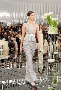 Chanel set its spring-summer 2017 haute couture collection at Grand Palais. With a decor featuring 1930's art deco style, models walked on mirrored tiles in Karl Lagerfeld's sleek designs. The collection opened up with tweed suits in fitted and tailored silhouettes, nipped at the waist. As the show progressed, curvy lines are enhanced with faux …