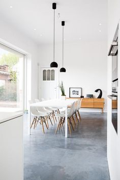 Open-plan kitchen-dining area with polished concrete floor. VillaKL. Photo by Tineke De Vos.