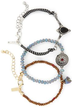 Accessorizing with a mix-and-match set of three beaded and cord bracelets from Topshop.