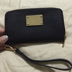 MK black Wristlet wallet MK Black Wristlet Wallet. Removable wrist strap holder. picture shows it's the size of a iPhone 6plus.   No Trades  Michael Kors Bags Clutches & Wristlets