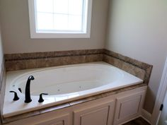 Downstairs master suite with a luxury bath that includes a double vanity, whirlpool tub, and separate tile shower. goldsbororealestatefinder.com