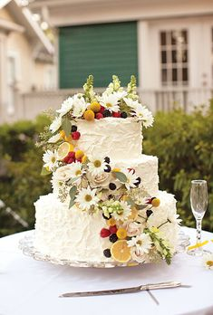 Red velvet wedding cake, by Cakes by Gina, decorated with a cascade of fresh flowers and fruit. Photo by Akil Bennett