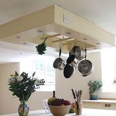 Utensil hanging  rack suspended over the freestanding kitchen island. If required this design can incorporate downlighters as shown. These can be made in different sizes as necessary to match the island dimensions. Shown here finished in Dulux Heritage Cream.