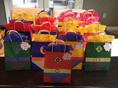 """DIY Pinterest inspired superhero goodie bags.  So easy and really cute.   Made from colored gift bags and basic shapes cut from construction paper.  You can personalize them with initials...or not.  Fantastic goody for our avengers party.  I also put a little bubble on them that said, """"Thanks for being a super friend."""""""
