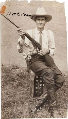 """[Texas Rangers]. Nat B. Jones Photograph, circa 1920. Nat Jones, who went by the nickname """"Kiowa,"""" sits on a box crate holding a lever action, .30 Army Winchester Model 1895, the ubiquitous Colt revolver (with ivory handles) holstered on his right hip.:"""