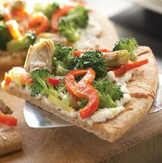 Roasting the broccoli, artichokes, squash and peppers in garlickly olive oil is the key to making this Roasted Vegetable Pizza so delicious. Slice this meatless pizza in narrow wedges to serve as an appetizer.