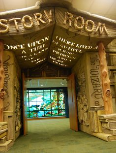 Brentwood Library    [Image is of the doorway to the Story Room, the walls of which look like giant books sculpted with scenes from the story on their covers and with an awning made to resemble an open book facedown over the walkway, the opening lines of a fairy tale glowing from it.]