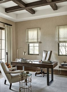 Neutral home office with grasscloth wallpaper and stained coffered ceiling beams.