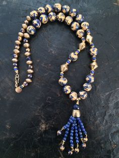 spectacular creation, made primarily of gold-washed lapis lazuli beads with dragon designs carved into each bead. Smaller faceted lapis beads and a bronze cone are used to create the pendant. More faceted lapis beads with gold-filled bead caps and hook and eye clasp finish the piece.