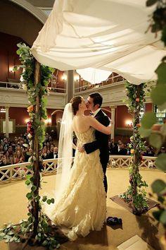 Sixth & I: A couple shares a kiss under the chuppah.