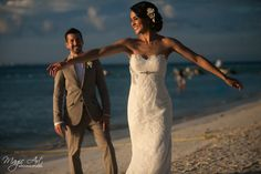 Happy beach bride poses in her strapless lace wedding gown. Magic Art Studio in Cancun, Mexico.