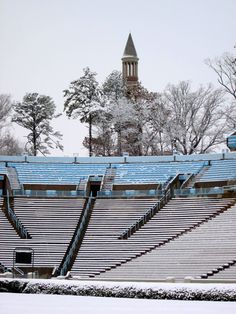 A snow covered Kenan Stadium with the Bell Tower in the distance.