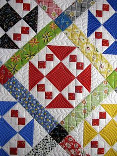 The quilting on this is fantastic.  Love the center square of each block and the feathers