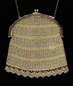 This evening bag with chain metal links has a silver coloured Greek key pattern running across it. During the late 19th Century, Germany was the major centre for making metal bags like this one. Circa 1900.