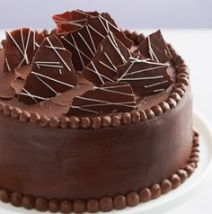 Nothing is wrong with a chocolate cake with chocolate frosting, right? To make those chocolate shards that decorate the top of the cake, melt chocolate and spread it thinly and evenly on a piece of parchment paper. When it has hardened, carefully break it into pieces.